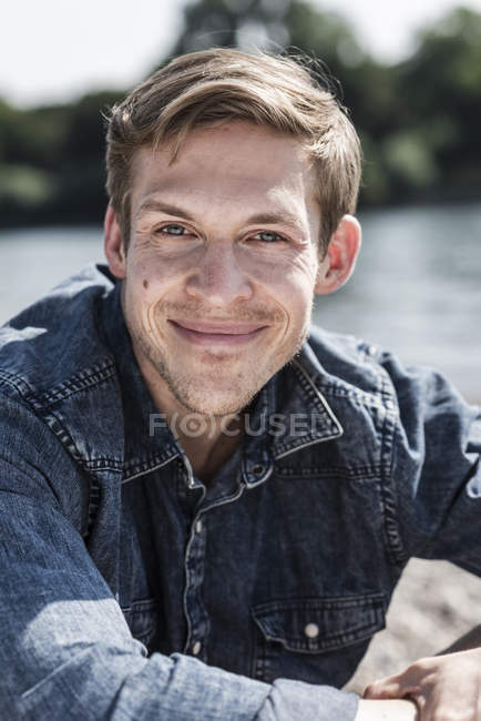 Portrait of smiling man sitting outdoors in summer — Stock Photo