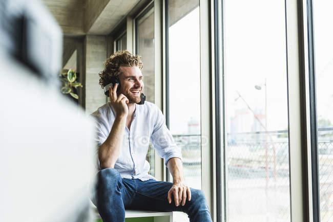 Heureux jeune homme occasionnel écoutant de la musique avec écouteurs à la fenêtre — Photo de stock