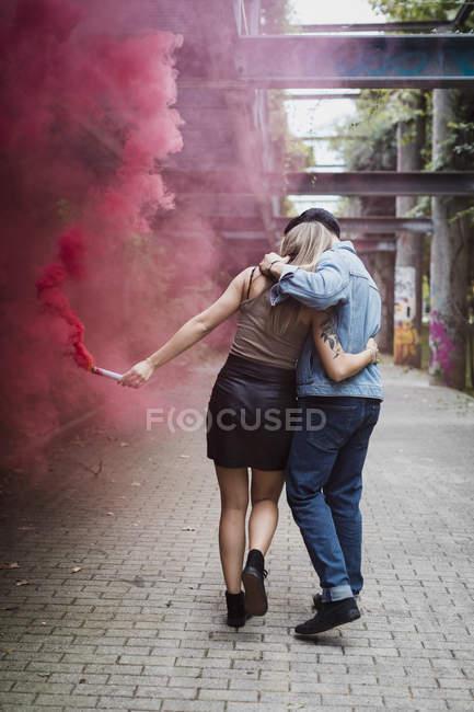 Молодая пара с дымовой горелкой выходит на улицу — стоковое фото