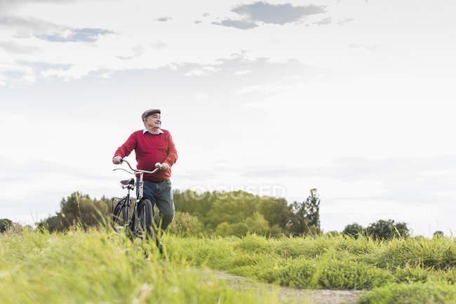 Seniorin schiebt Fahrrad auf Fußweg im ländlichen Raum — Stockfoto