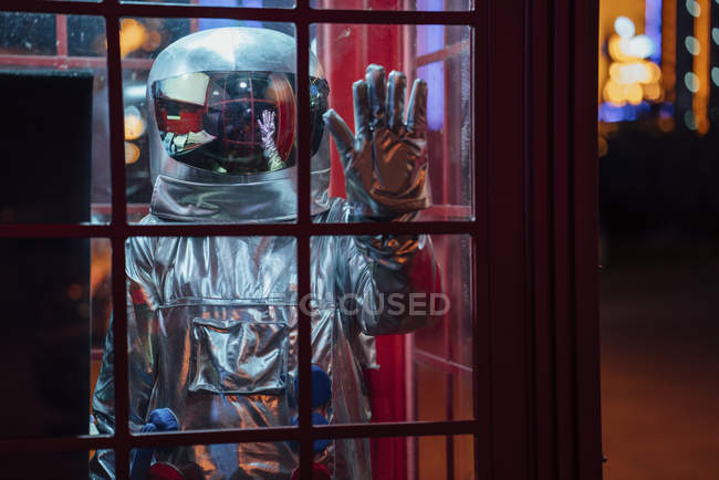 Spaceman trapped in telephone box at night — Stock Photo