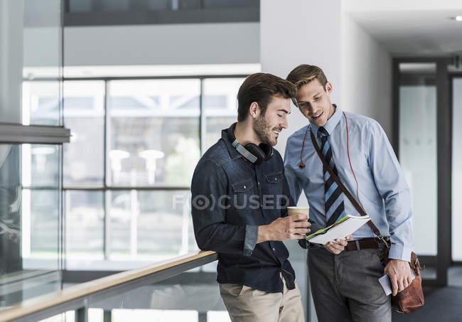 Dos colegas hablando en el piso de la oficina - foto de stock