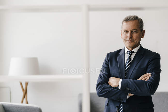 Portrait of mature businessman with arms crossed in office — стокове фото