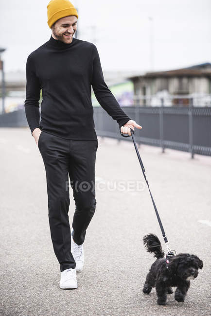 Fashionable young man walking with dog on a bridge — Stock Photo