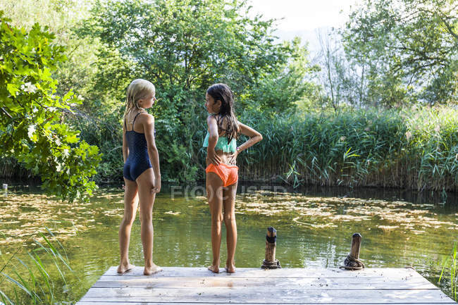 Two girls standing on jetty at a pond talking — Stockfoto