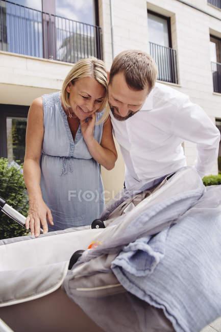 Glückliches Paar schaut in Kinderwagen auf der Straße — Stockfoto