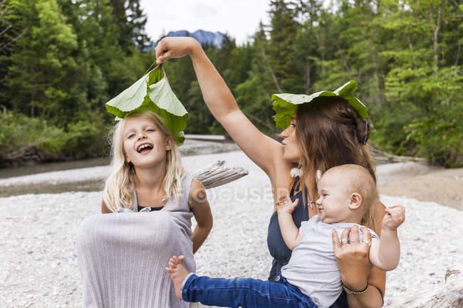 Mãe com dois filhos brincando com folhas na beira do rio — Fotografia de Stock