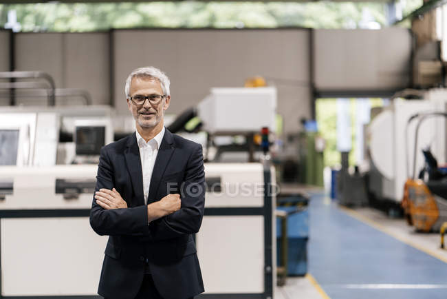 Portrait of successful entrepreneur in company with arms crossed — Stock Photo