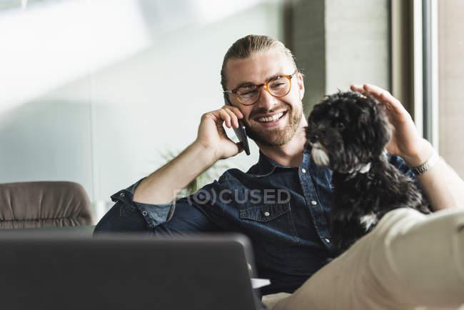 Jovem empresário sorridente com cachorro no celular no escritório — Fotografia de Stock
