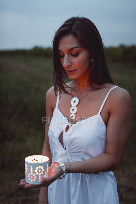 Young woman in nature, holding candle in the evening — Stock Photo