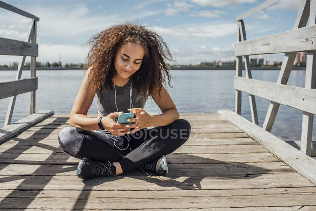 Young athletic woman sitting at riverside and using smartphone — Stock Photo