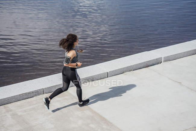 Jeune femme athlétique courant au bord de la rivière — Photo de stock
