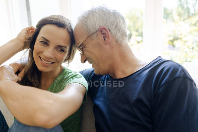 Happy mature couple sitting on couch at home — Stock Photo