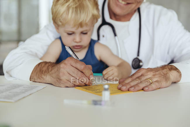 Toddler sitting on doctor's lap, while filling in immunization card — Stock Photo