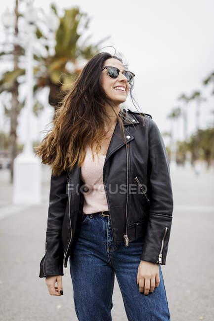 Felice giovane donna in piedi sulla strada in città — Foto stock