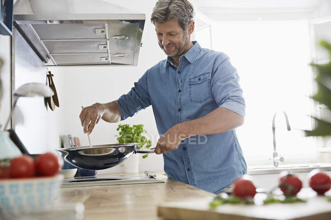 Mature man in kitchen frying vegetables — Stockfoto