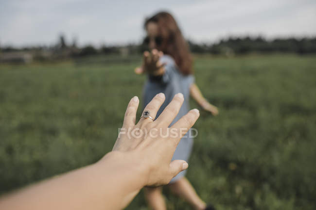 Hand reaching out for woman on a field — Stock Photo