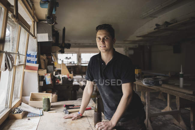 Porträt eines lächelnden Tischlers mit einer Flasche Bier in der Werkstatt — Stockfoto
