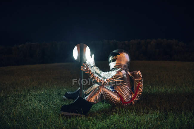 Spaceman sitting on meadow at night and looking at lamp — Stock Photo