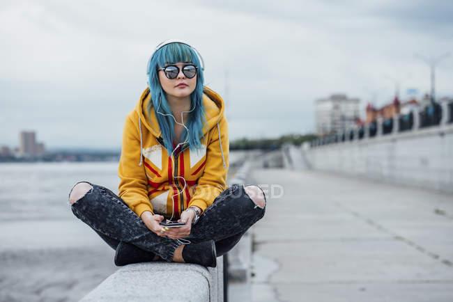 Молодая женщина с окрашенными голубыми волосами сидит на стене и слушает музыку в наушниках и смартфоне — стоковое фото