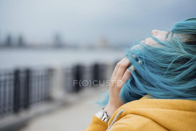 Молодая женщина с голубыми волосами смотрит вверх — стоковое фото