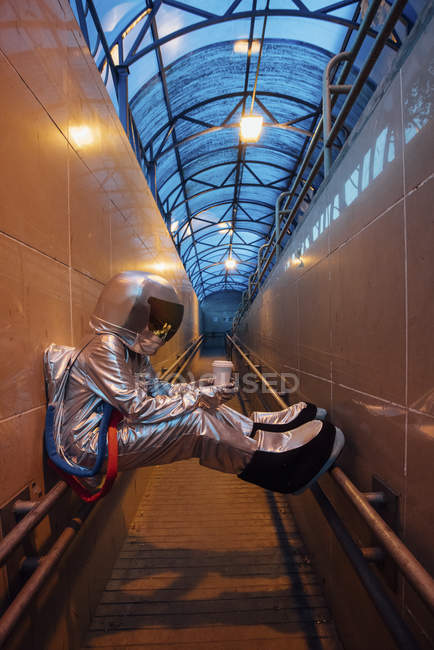 Spaceman in city at night with takeaway coffee sitting on railing in narrow passageway — Stock Photo