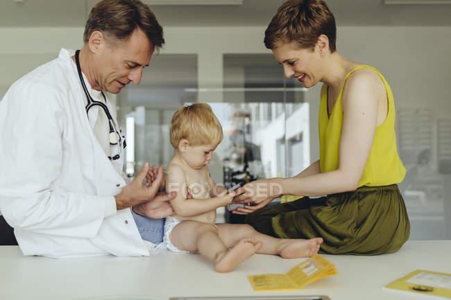 Pediatra vacinando a criança, injetando o braço da criança, observando a mãe — Fotografia de Stock
