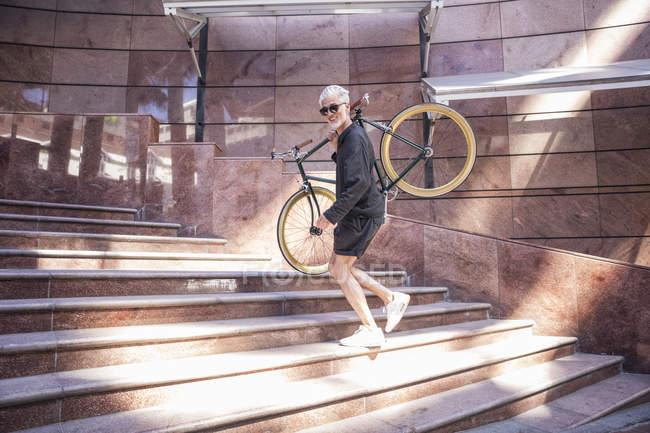 Homem maduro carregando bicicleta no ombro na escada do edifício — Fotografia de Stock