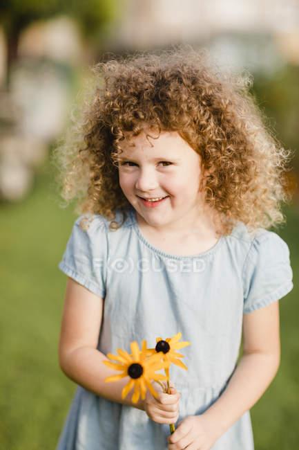 Retrato de menina feliz com flores colhidas no jardim — Fotografia de Stock