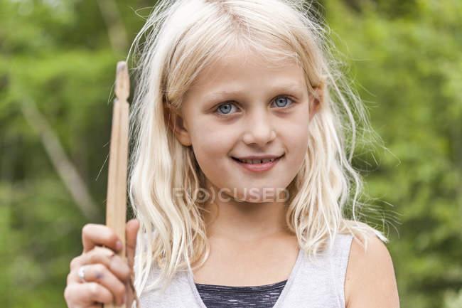 Портрет усміхненої дівчини, що тримає дерев