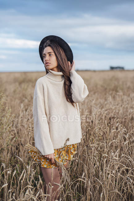 Portrait of young woman wearing hat and oversized turtleneck pullover standing in corn field — Photo de stock
