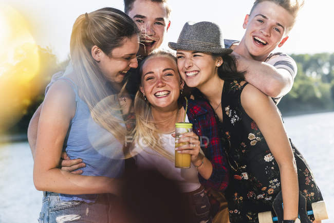 Retrato del grupo de amigos felices a orillas del río - foto de stock