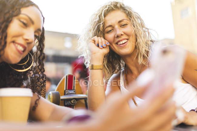 Heureuses amies partageant un téléphone portable à l'extérieur — Photo de stock