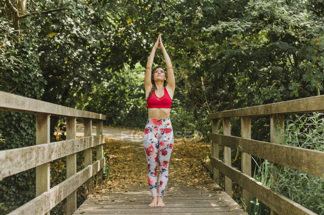Young woman practicing Pilates in urban park — Stock Photo