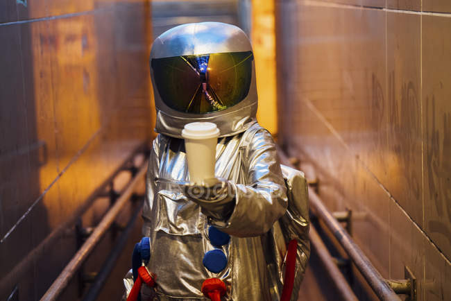 Spaceman in city at night with takeaway coffee in narrow passageway — Stock Photo