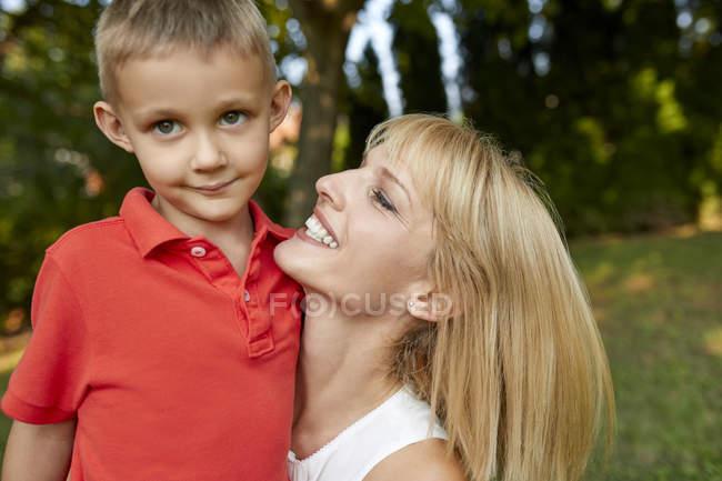 Mère heureuse portant son fils dans le jardin — Photo de stock