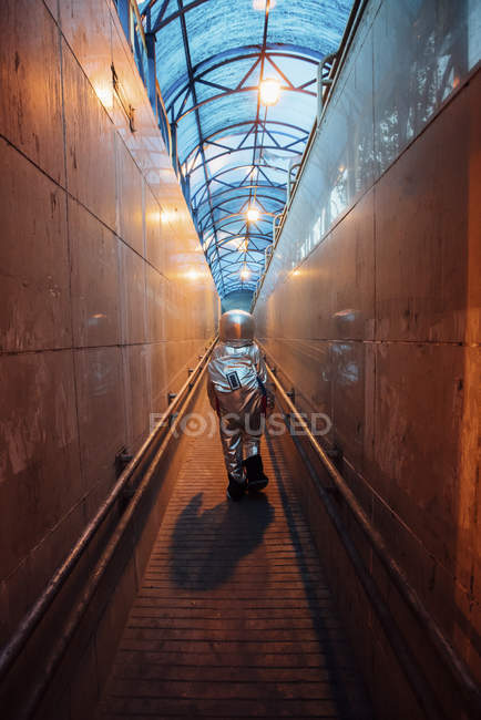 Rear view of spaceman in city at night walking in narrow passageway — Stock Photo