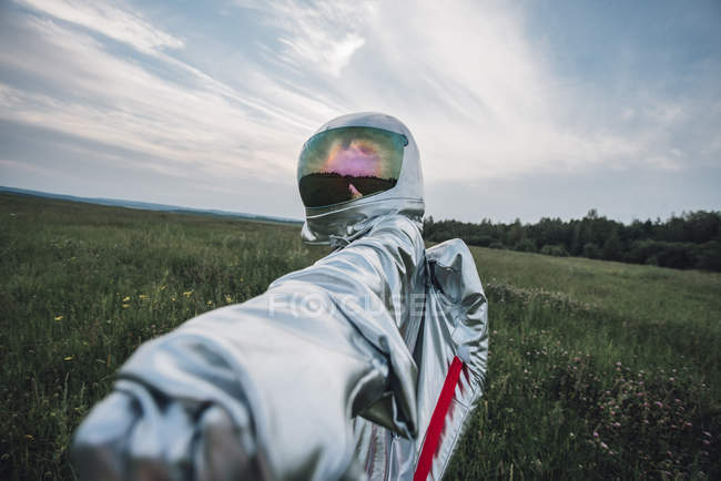 Spaceman exploring nature, reaching out hand in meadow — Stock Photo
