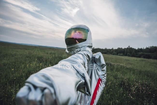Spaceman que explora a natureza, alcangando para fora a mão no Prado — Fotografia de Stock