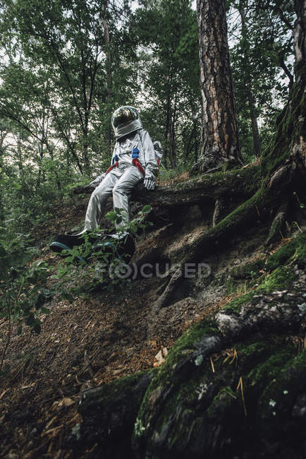 Spaceman exploring nature, sitting on tree roots in forest — Stock Photo