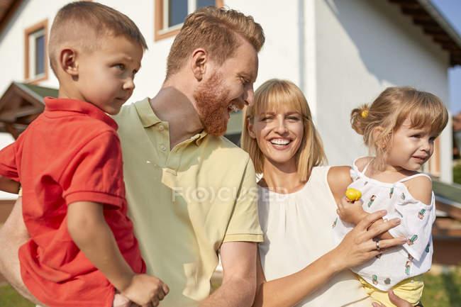 Портрет щасливої сім'ї в саду свого будинку — стокове фото