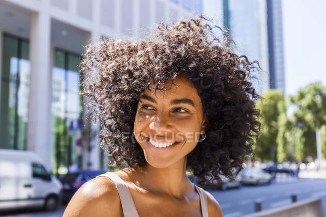 Portrait of laughing young woman with curly hair in city — Stock Photo