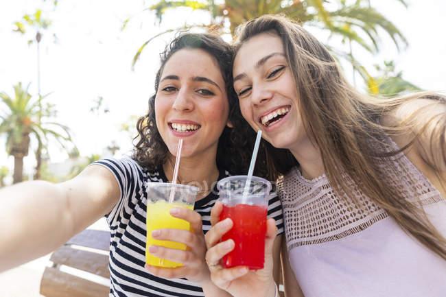 Портрет двух счастливых подруг, наслаждающихся свежей слезой — стоковое фото