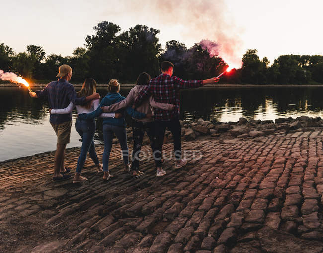 Group of friends walking at the riverside in the evening with torches — Stock Photo
