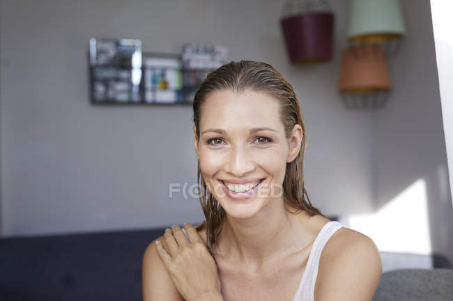 Portrait of laughing blond woman with wet hair at home — Stock Photo