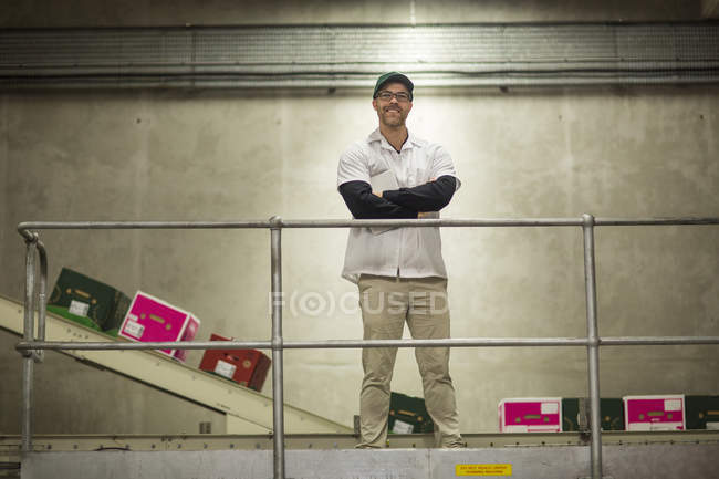 Worker standing in apple factory — Stock Photo