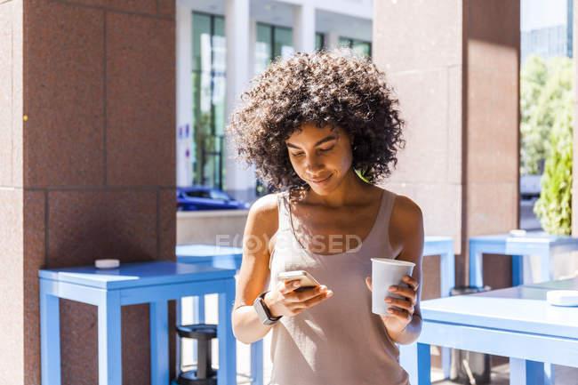 Lächelnde junge Frau mit Kaffee zum Handy in der Stadt — Stockfoto