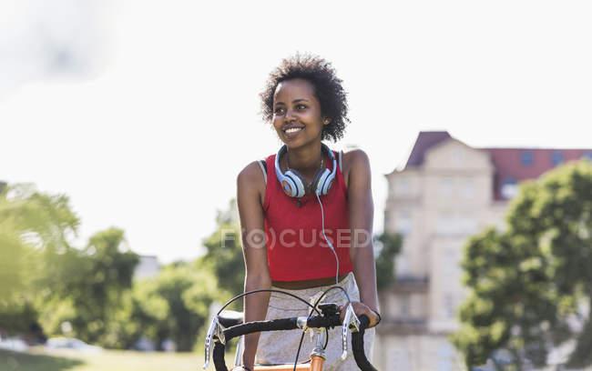 Sonriente joven deportiva en bicicleta en el parque - foto de stock