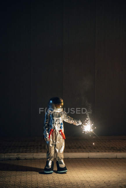 Spaceman standing on road at night and holding sparkler — Stock Photo
