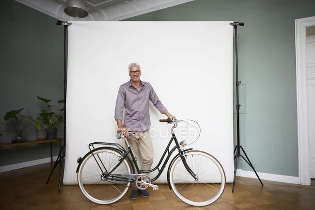 Porträt eines reifen Mannes, der mit Fahrrad an der Projektionswand posiert — Stockfoto